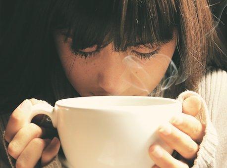 コーヒーの香りを楽しむ女性